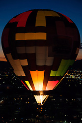 """Dawn Patrol 12"" - Photograph of a glowing hot air balloon flying for the Dawn Patrol at the 2012 Great Reno Balloon Race. Photographed from a hot air balloon."