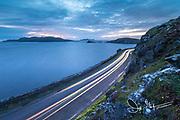 A cars headlights illuminate the narrow road out to Slea Head, Dingle Peninsula, County Kerry, Ireland.