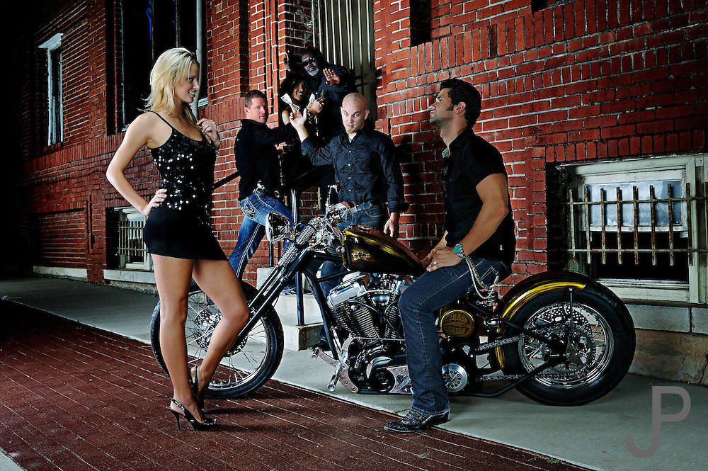 Brass Ball Bobber motorcycle in urban setting, with hot chick in foreground.  Club scene with background participants looking at bike.  Model and product released.