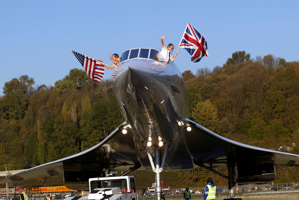 A British Airways Concorde passenger jet is towed on the rampway at Boeing Field in south Seattle on Wednesday, November 5, 2003 in Seattle, Washington while co-pilot Cpt. Les Brodie, left, and pilot Cpt. Mike Bannister, right, wave flags. This Concorde was donated after decommisioning by British Airways and is one of four outside of Europe and the only one on the west coast of the United States. The pilot, Cpt. Mike Bannister, broke the world speed record from New York to Seattle on this historic last flight with by going supersonic over Canada for a time of 3 hours, 55 minutes, and 12 seconds. (Photo by Tim Matsui/Getty Images)
