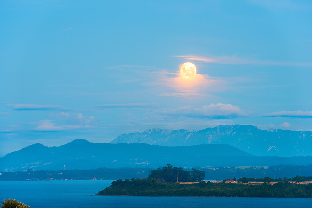 Moon rising between the clouds over Lake Llanquihue, X Region de Los Lagos, Chile
