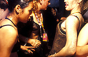 Girls covered in mud dancing, T in the park festival, UK 2000's