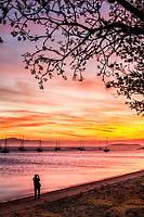 Silhueta de homem fotografando o por do sol na Praia de Santo Antonio de Lisboa. Florianópolis, Santa Catarina, Brasil. / <br /> Silhouette of a man taking pictures of Santo Antonio de Lisboa Beach at sunset. Florianopolis, Santa Catarina, Brazil.