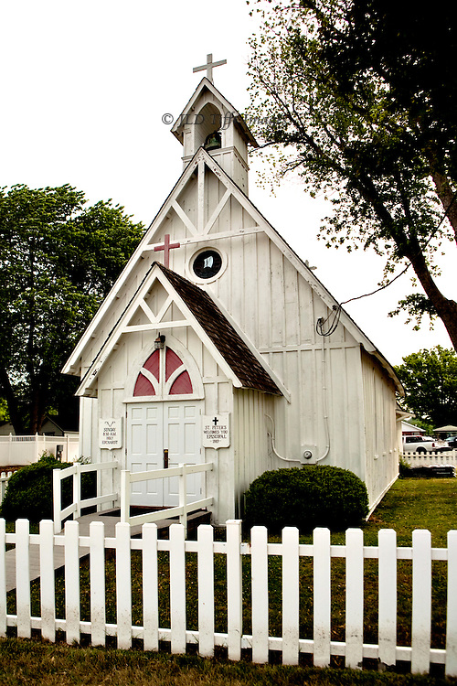 Three-quarter perspective view of the tiny wooden St. Peter's Episcopal Church in the village of Solomon's Island, MD. A white picket fence underlines the structure visually.