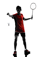 one asian badminton player young man at service in silhouette isolated white background