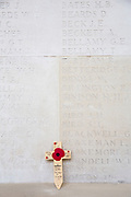 A memorial cross with a poppy on it placed up against the wall, containing the names of hundreds of fallen soldiers that died during the First and Second World War. Faubourg D'Amiens cemetery is the burial site of 2678 identified casualties and a memorial to thousands more from the First and Second World War.  It is looked after and managed by the Commonwealth War Graves Commission in the town of Arras, France. (photo by Andrew Aitchison / In pictures via Getty Images)