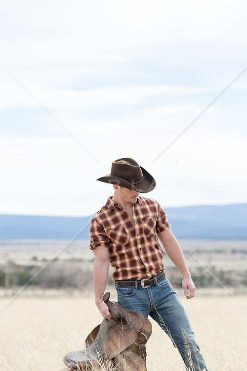cowboy with a saddle in a field on a ranch