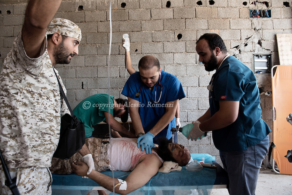 Libya, Sirte: Inside an under construction building a doctor carries out a heart massage to a fighter sympathising with Libya's Government of National Accord's (GNA) injured on the head during heavy clashes with ISIS in Sirte. Alessio Romenzi