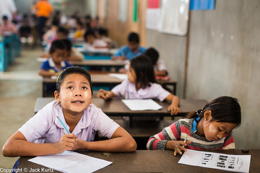 06 MARCH 2014 - MAE SOT, TAK, THAILAND: A girl thinks about her answer on her final exam for the semester at the Sky Blue School. There are approximately 140 students in the Sky Blue School, north of Mae Sot. The school is next to the main landfill for Mae Sot and serves the children of the people who work in the landfill. The school relies on grants and donations from Non Governmental Organizations (NGOs). Reforms in Myanmar have alllowed NGOs to operate in Myanmar, as a result many NGOs are shifting resources to operations in Myanmar, leaving Burmese migrants and refugees in Thailand vulnerable. The Sky Blue School was not able to pay its teachers for three months during the current school year because money promised by a NGO wasn't delivered when the NGO started to support schools in Burma. The school got an emergency grant from the Burma Migrant Teachers' Association and has since been able to pay the teachers.      PHOTO BY JACK KURTZ
