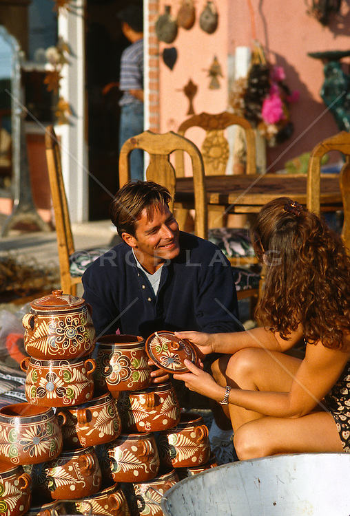 couple looking at mexican pottery while at an outdoor store