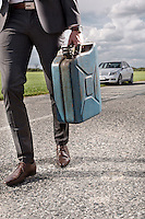 Low section of young businessman carrying gas can with broken car in background at countryside