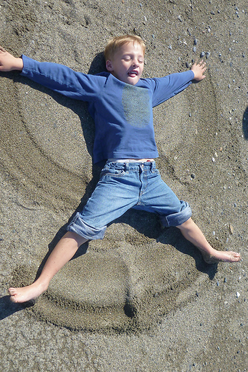A young boy has fun making a sand angel on the beach in Gustavus. MR