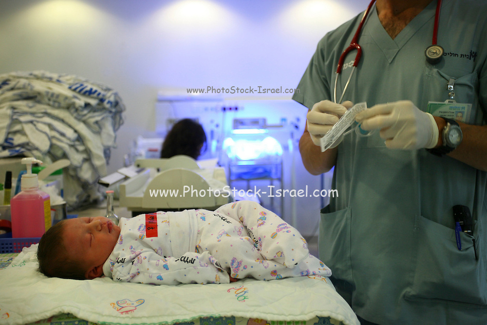 A baby girl is getting her first vaccination at the hospital, few hours after birth.