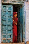 Woman wearing their traditional sarees and silver jewellery outside traditional sand stone houses of Jaisalmer. Rajasthan, INDIA<br /> Heavy ankle bracelets are common as well as nose rings and silver bangles.<br /> Founded in 1156 Jaisalmer grew to be a major staging post on the trade route across the forbidding Thar desert from India to the west. It is known as the Golden City as the fort and town's buildings are built from the local yellow sandstone. The bustling narrow streets are lined with tradesmen selling their wares. Many of the smalll shops are occupied by descendents of the original owners. There are many exceptional Havelis (mansions of rich merchants - exquistely carved) both in the fort and the old walled town.