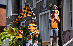 A family of Wolverhampton Wanderers fans wave flags during the winner's parade through Wolverhampton.