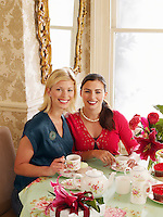 Two young women sitting at dining table portrait elevated view