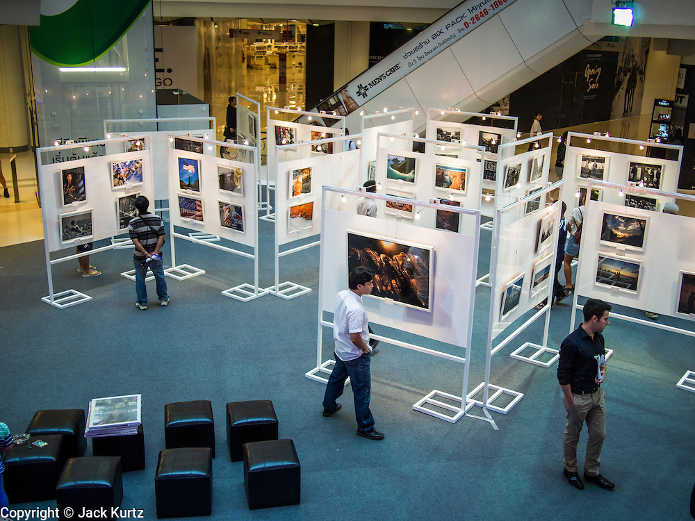 19 JULY 2013 - BANGKOK, THAILAND:  Workers from the US Embassy in Bangkok hang photos for an exhibit in CentralWorld in Bangkok. The US Embassy in Bangkok sponsored the photo exhibit, which celebrates 180 years of US-Thai diplomatic relations. There are 180 photos hanging in the show, 90 by American photographers in Thailand and 90 by Thai photographers in the United States. The show, which opened July 19, is hanging in CentralWorld, a large mall in Bangkok, and is touring Thailand when it concludes its Bangkok run on July 21.    PHOTO BY JACK KURTZ
