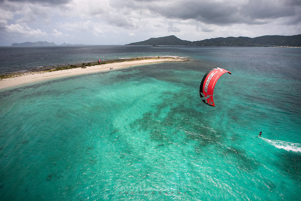 Kiteboarder explores an uninhabited island from the vessel Discovery, on the Best Odyssey expedition near Grenada in the Caribbean.  A perfect white sand beach provides great contrast to the aqua colors and menacing sky.
