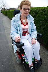 Older woman wheelchair user going down the road,