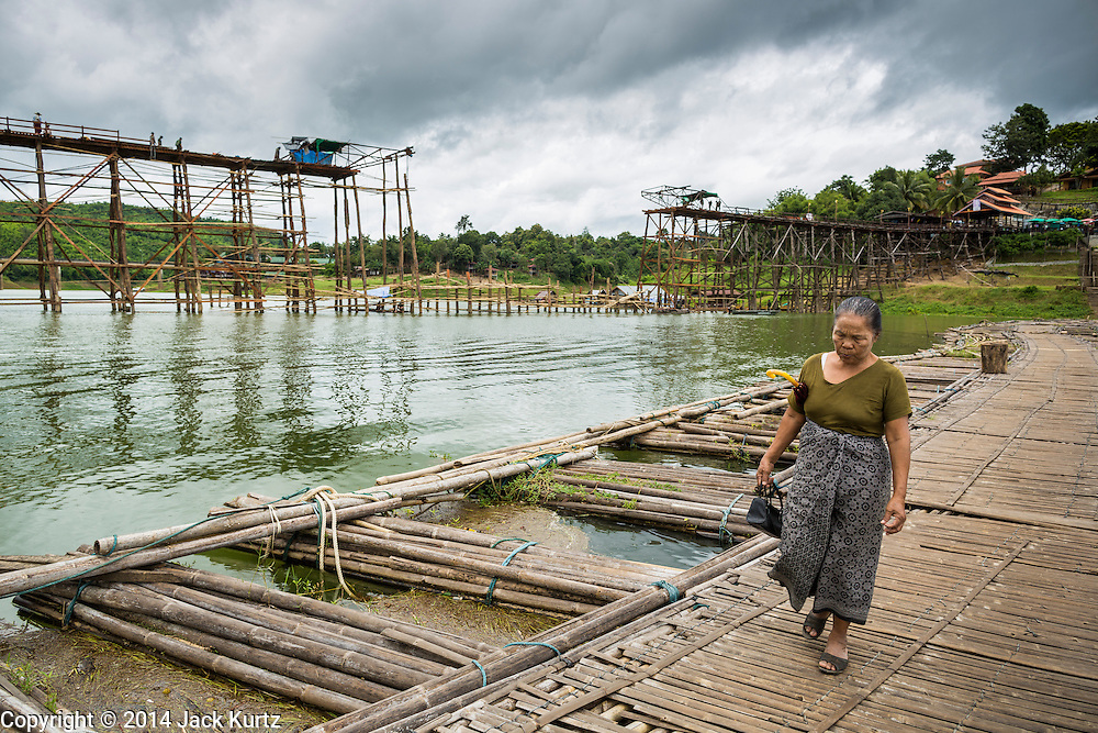 17 SEPTEMBER 2014 - SANGKHLA BURI, KANCHANABURI, THAILAND: A woman walks along the temporary bamboo bridge the Mon community is using while the Mon Bridge, in the background, is being repaired. The 2800 foot long (850 meters) Saphan Mon (Mon Bridge) spans the Song Kalia River. It is reportedly second longest wooden bridge in the world. The bridge was severely damaged during heavy rainfall in July 2013 when its 230 foot middle section  (70 meters) collapsed during flooding. Officially known as Uttamanusorn Bridge, the bridge has been used by people in Sangkhla Buri (also known as Sangkhlaburi) for 20 years. The bridge was was conceived by Luang Pho Uttama, the late abbot of of Wat Wang Wiwekaram, and was built by hand by Mon refugees from Myanmar (then Burma). The wooden bridge is one of the leading tourist attractions in Kanchanaburi province. The loss of the bridge has hurt the economy of the Mon community opposite Sangkhla Buri. The repair has taken far longer than expected. Thai Prime Minister General Prayuth Chan-ocha ordered an engineer unit of the Royal Thai Army to help the local Mon population repair the bridge. Local people said they hope the bridge is repaired by the end November, which is when the tourist season starts.    PHOTO BY JACK KURTZ