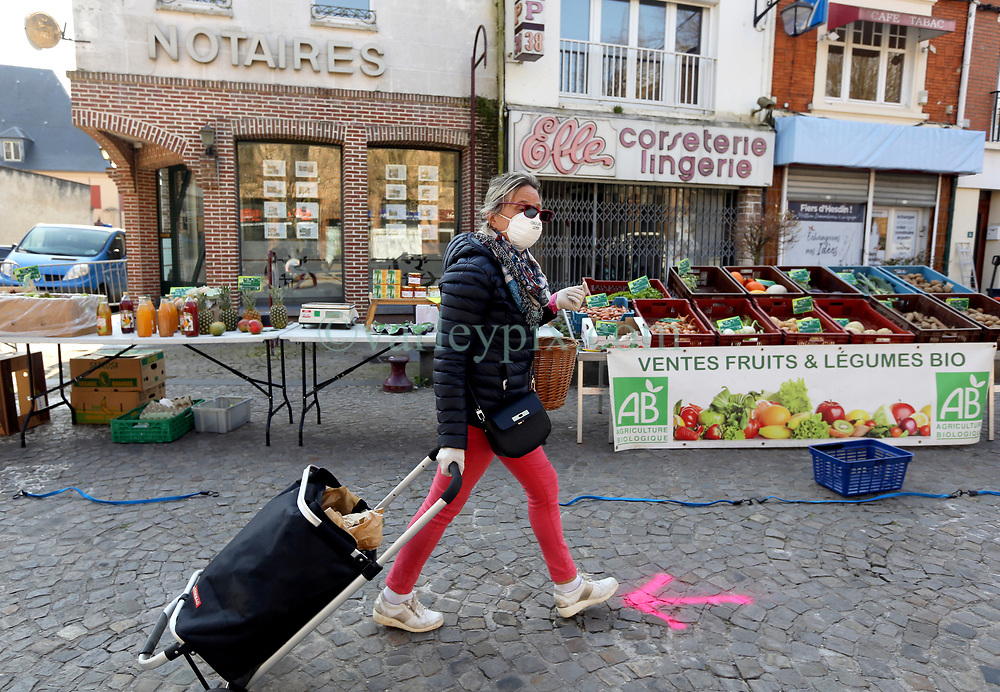 02 April 2020. Hesdin, Pas de Calais, France. <br /> Coronavirus - COVID-19 in Northern France.<br /> <br /> Easing restrictions on local markets. Shopper in mask. For the first time since government restrictions came into force, the main market in Hesdin has been permitted to re-open. The historical town has hosted a usually vibrant and bustling market since the middle ages. With stall holders limited and many suffering huge financial losses, those selling food today were happy to be back to work despite the ongoing risks posed by coronavirus.<br /> <br /> Shoppers, many wearing masks were mostly maintaining their social distancing with people happy to be out and able to meet and talk with other people. A lot of shoppers were elderly people who have been trapped in their homes for weeks. One shopper complained of 'la misère,' - the misery of this virus and being stuck in her home. <br /> <br /> Anyone leaving their home must carry with them an 'attestation,' in a effect a self administered permit to allow them out of the house. If stopped by the police, one must produce a valid permit along with identification papers. Failure to do so is punishable with heavy fines. Movement in France has been heavily restricted by the government and today's market re-opening was a brief return to normalcy for many able to escape the confines of their homes.<br /> <br /> Photo©; Charlie Varley/varleypix.com