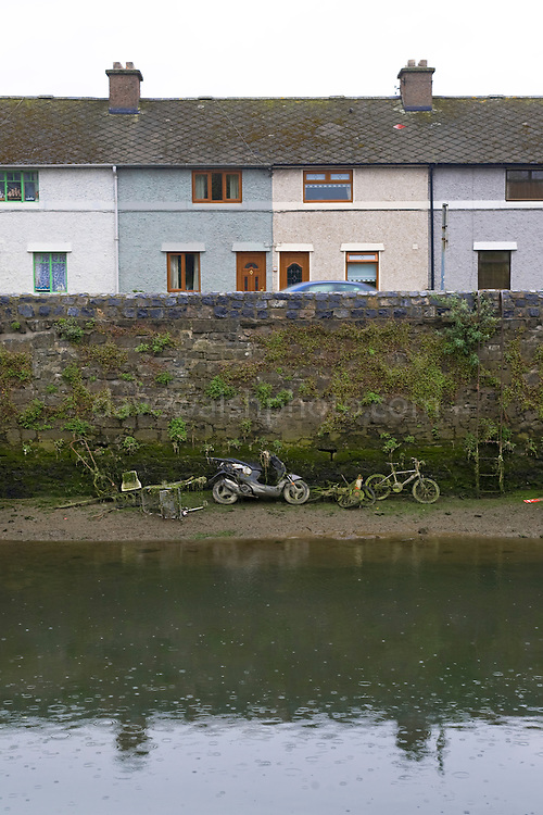A moped, bicycle, and other dumped items in the River Tolka, Dublin, at low tide. Someone seems to have collected them, but not removed them.