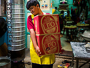 "12 FEBRUARY 2018 - BANGKOK, THAILAND: A worker carries boxes of fresh steamed buns to a waiting delivery person in a home that makes steamed Chinese buns, called ""bao"" in the Chinatown neighborhood of Bangkok. Bao are eaten at midnight on the Lunar New Year and served to guests during New Year's entertaining. The buns are shipped out in recycled beer cartons. Lunar New Year, also called Tet or Chinese New Year, is 16 February this year. The coming year will be the Year of the Dog. Thailand has a large Chinese community and Lunar New Year is widely celebrated in Thailand, especially in Bangkok and large cities with significant Chinese communities.    PHOTO BY JACK KURTZ"