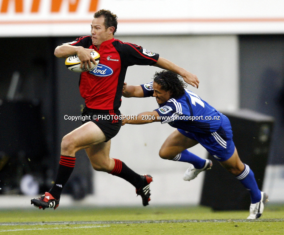 Leon MacDonald tackled by Tasesa Lavea during the 2006 Super 14 Rugby Union match between the Crusaders and the Blues at Jade Stadium, Christchurch, on Saturday 4 March 2006. Photo: Anthony Phelps/PHOTOSPORT
