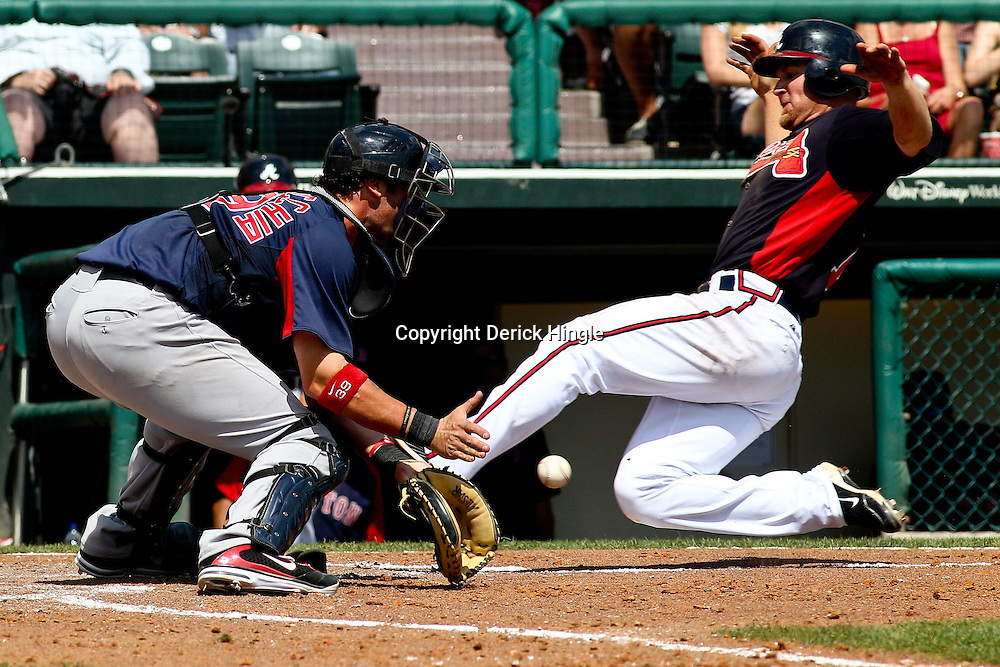 March 16, 2011; Lake Buena Vista, FL, USA; Atlanta Braves second baseman Brooks Conrad (7) slides past Boston Red Sox catcher Jarrod Saltalamacchia (39) for a run during a spring training exhibition game at the Disney Wide World of Sports complex. Mandatory Credit: Derick E. Hingle-US PRESSWIRE