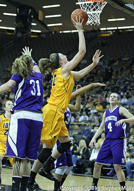 December 30, 2011: Iowa Hawkeyes center Morgan Johnson (12) puts up a shot between Northwestern Wildcats forward/center Dannielle Diamant (31) and Northwestern Wildcats guard Tailor Jones (34) during the NCAA women's basketball game between the Northwestern Wildcats and the Iowa Hawkeyes at Carver-Hawkeye Arena in Iowa City, Iowa on Wednesday, December 30, 2011.