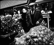Moore Street, Dublin.      (J97)..1975..23.12.1975..12.23.1975..23rd December 1975..For well over a hundred years Moore Street has served the citizens of Dublin. The longest running open air fruit and vegatable market offers value for money,particularly to those where money is in short supply. Predominately a fruit and veg market there are several traders who sell fish and seasonal goods, as illustrated by the photographs showing turkeys and holly wreaths being sold on the run up to Christmas..Decisions,Decisions this customer is pictured deciding what he wishes to purchase.