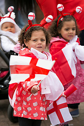 © Licensed to London News Pictures. 23/04/2015. Nottingham, UK. The Nottingham St George's parade took part today. The parade met in Forest Recreation Ground. An estimated two hundred people with trucks playing patriotic music and horses dressed in flags made their way along the streets into the City Centre. Pictured, a flag waving family. Photo credit : Dave Warren/LNP