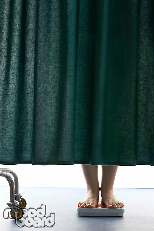 Person on weighing scales behind curtain in hospital low section