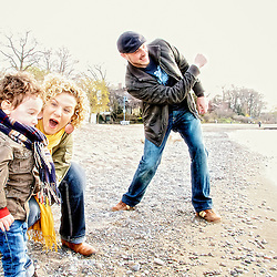 A family plays together at the beach waterfront.