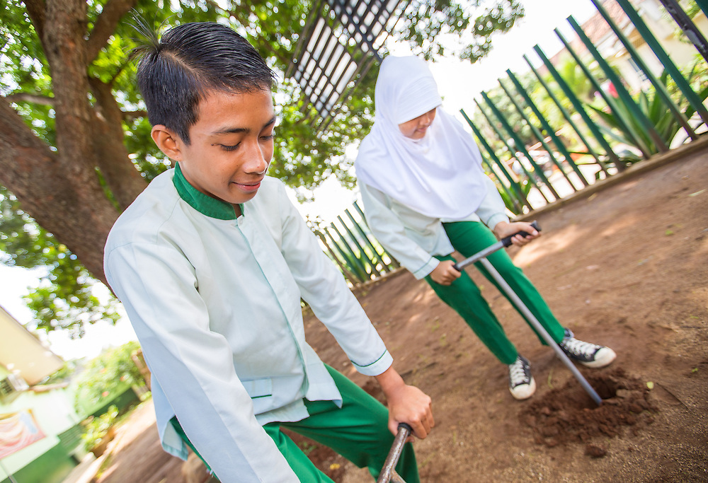 CAPTION: In addition to learning about the causes and effects of climate change in class, students are required to spend two to three hours a week implementing practical adaptation and mitigation solutions around school. In this picture, Dwi and her classmate Bagus are installing biopores outside their classroom. This takes less than an hour to complete, and the only tool required is a kind of long, T-shaped spade. By increasing the soil's re-absorption capacity, biopores play an effective role in reducing the risk of flooding. LOCATION: SMP N 7 School, Bandar Lampung, Indonesia. INDIVIDUAL(S) PHOTOGRAPHED: Bagus Murti (left) and Dwi Wijayanti (right) .
