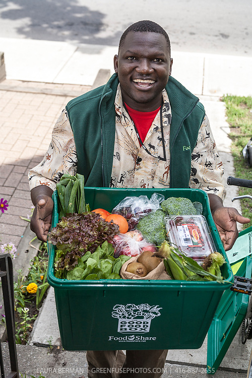 FoodShare staff Morris delivers a large Good Food Box to customers Anna and Phillip.