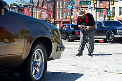 Sheldon Omar - Abba, 34, co-organizer and photographer sets uphill analog camera to make a photo of a classic car as members of the local classic and American muscle car community gathers for a meet on a North Philadelphia, on Sunday.