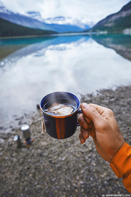 The perspective of a right-handed man holding a hot cup of tea at a snowy, mountain lake shore.