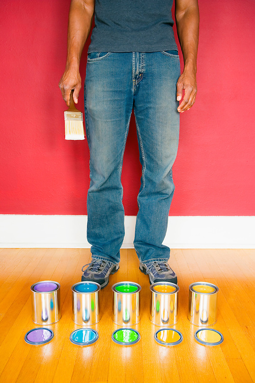 African American man standing over a selection of varying paint cans holding a paint brush..Model release: 20060425_MR_A.Prperty Release: 20060425_PR_A
