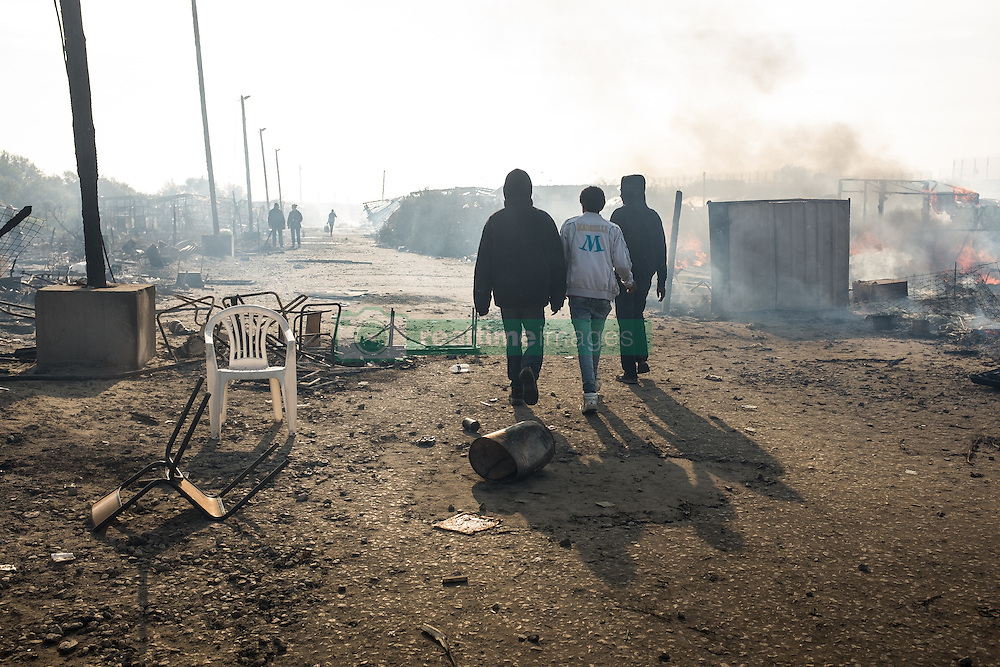 October 26, 2016 - Calais, France - Migrants walk between burned down huts in the Calais Jungle, on October 26, 2016. Huge fires destroyed a mayor part of the refugee camp today. (Credit Image: © Markus Heine/NurPhoto via ZUMA Press)