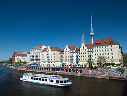 Tourist river tour boat passes historic Nikolaiviertel district of Berlin Germany