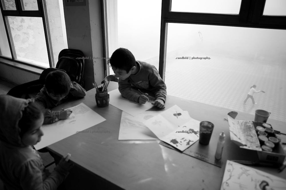 "kids draw and paint on a foggy day in the Narecatsi Cultural center. This image is part of the photoproject ""The Twentieth Spring"", a portrait of caucasian town Shushi 20 years after its so called ""Liberation"" by armenian fighters. In its more than two centuries old history Shushi was ruled by different powers like armeniens, persians, russian or aseris. In 1991 a fierce battle for Karabakhs independence from Azerbaijan began. During the breakdown of Sowjet Union armenians didn´t want to stay within the Republic of Azerbaijan anymore. 1992 armenians manage to takeover ""ancient armenian Shushi"" and pushed out remained aseris forces which had operate a rocket base there. Since then Shushi became an ""armenian town"" again. Today, 20 yeras after statement of Karabakhs independence Shushi tries to find it´s opportunities for it´s future. The less populated town is still affected by devastation and ruins by it´s violent history. Life is mostly a daily struggle for the inhabitants to get expenses covered, caused by a lack of jobs and almost no perspective for a sustainable economic development. Shushi depends on donations by diaspora armenians. On the other hand those donations have made it possible to rebuild a cultural centre, recover new asphalt roads and other infrastructure. 20 years after Shushis fall into armenian hands Babies get born and people won´t never be under aseris rule again. The bloody early 1990´s civil war has moved into the trenches of the frontline 20 kilometer away from Shushi where it stuck since 1994. The karabakh conflict is still not solved and could turn to an open war every day. Nonetheless life goes on on the south caucasian rocky tip above mountainious region of Karabakh where Shushi enthrones ever since centuries."