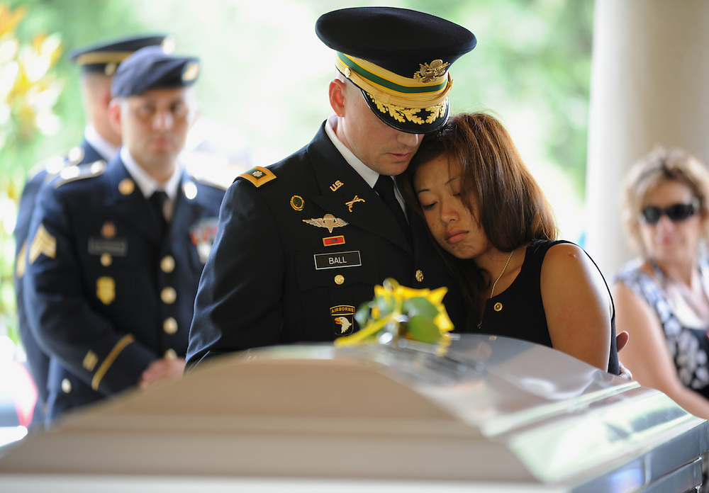 Sunny Seija the wife of Staff Sgt. Ricardo Seija is comforted by Lt. Col. Richard Ball during Seija's funeral services Wednesday, July 18, 2012 at Florida National Cemetery in Bushnell. Seija was one of two local soldiers killed July 8 when their armored vehicle hit an IED in Afghanistan. Six soldiers died in that attack.