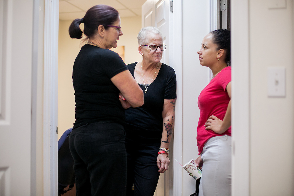 BROOKLYN, NY - JUNE 30, 2016: Connie Pentony-Brown and Donna Mae DePola, founder of The Resource Training Center, speak to client Alexis DeJesus at the counseling center in Bay Ridge, Brooklyn, New York. CREDIT: Sam Hodgson for The New York Times.