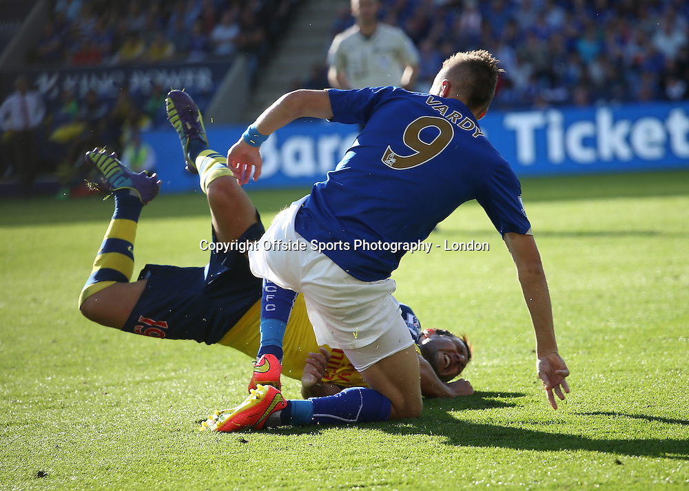 31 August 2014 Premier League Football - Leicester City v Arsenal  Santi Cazorla of Arsenal is brought down by a strong tackle from Jamie Vardy of Leicester.<br /> Photo: Mark Leech
