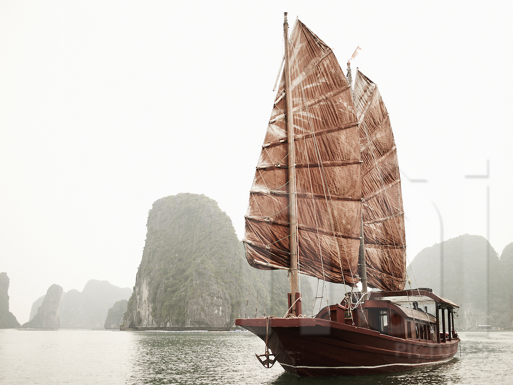 An old traditional junk with red sails cruise on the calm waters of Ha Long bay, a UNESCO world heritage site. Vietnam, Asia
