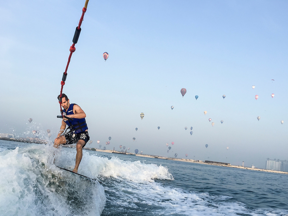 DUBAI, UAE — DECEMBER 5, 2015: Early morning wake surfing with hot air balloons in the background during the World Air Games **IPHONE**