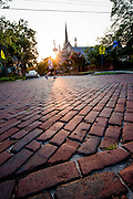 The sun sparkles past the First Presbyterian Church of Wilmington, NC as joggers run across the sun-soaked brick streets of downtown Wilmington.  PHOTO BY: JEFF JANOWSKI PHOTOGRAPHY