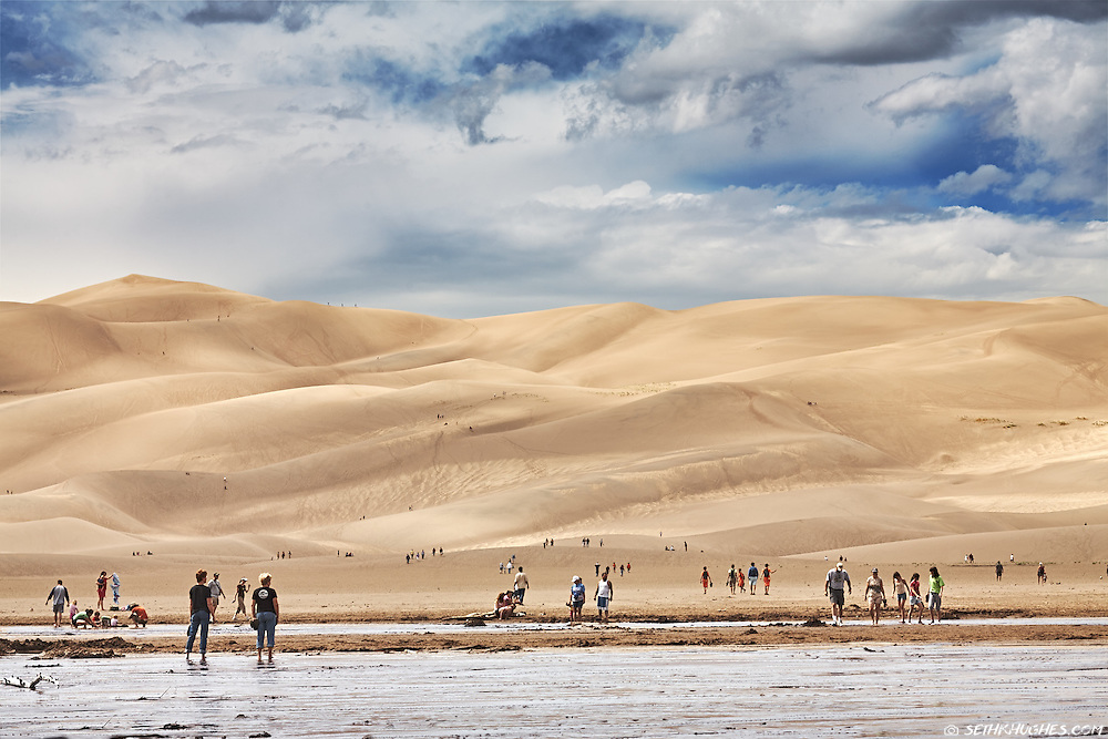 People cross the waters of Medano Creek and explore the dunes beyond during a warm day at Great Sand Dunes National Park, Colorado.