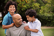 Mixed race father playing with sons